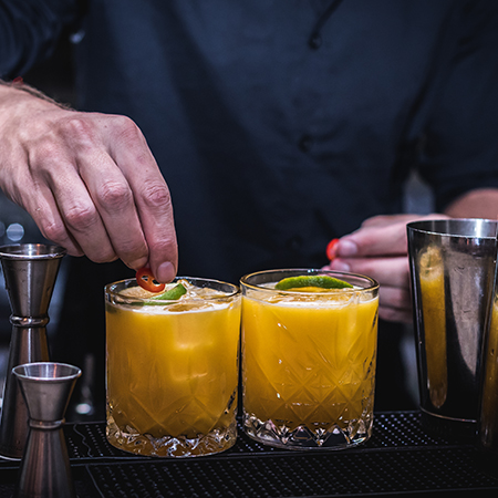 ברמן מכין קוקטייל בצבע צהוב בבר בסורה מרה - barman is making a yellow cocktail drink at the bar at Suramara