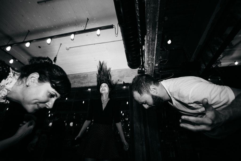 תמונה שחור לבן של 3 אנשים רוקדים באירוע בסורה מרה - Black and white photo of 3 people dancing at an event at Sura mara