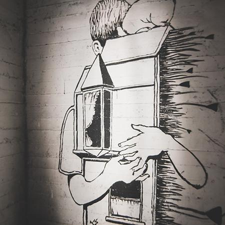ציור שחור לבן על קיר של ילד מחבק בית בסורה מרה - A black and white painting on the wall of a child hugging an house on a wall at Suramara