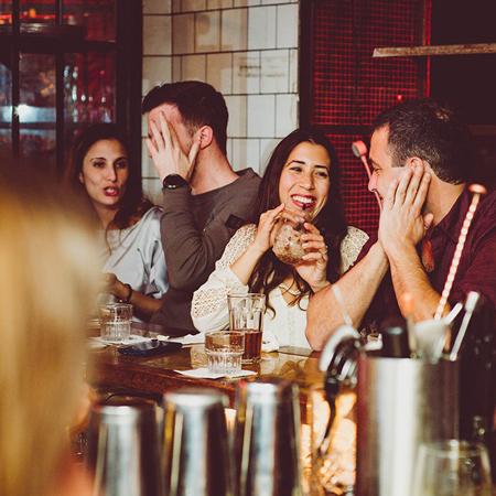 אנשים יושבים על הבר שותים ומחוייכים -פםק - people sitting at the bar drinking and smiling