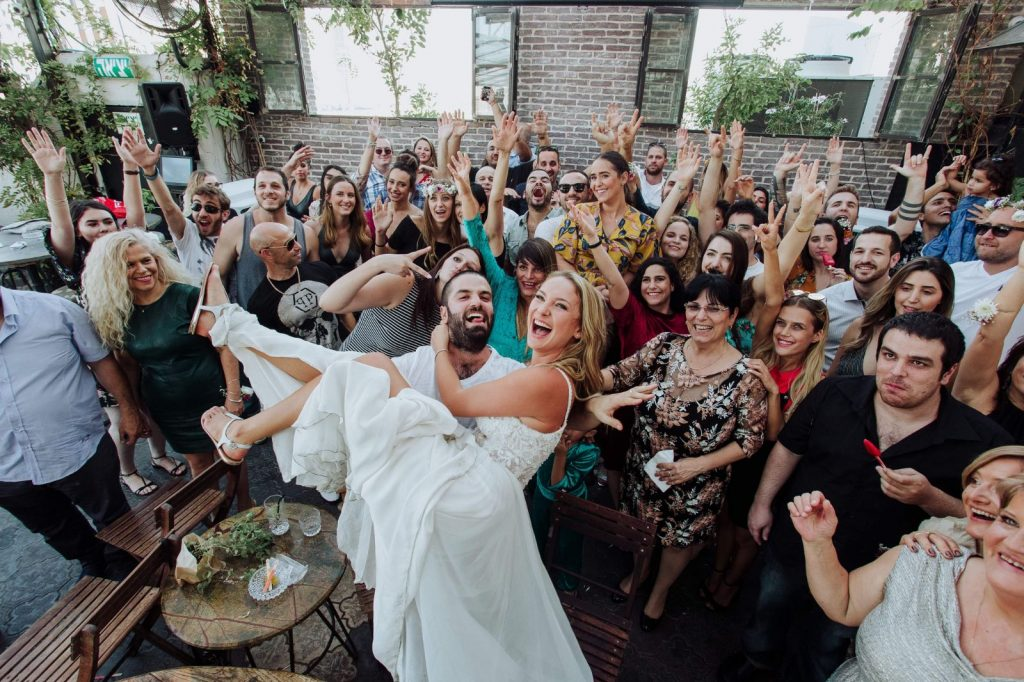 חתן מרים כלה שמסביבו הרבה אחורחים שמחים - שׁ ער- a groom lifts the bride with guests around all happy
