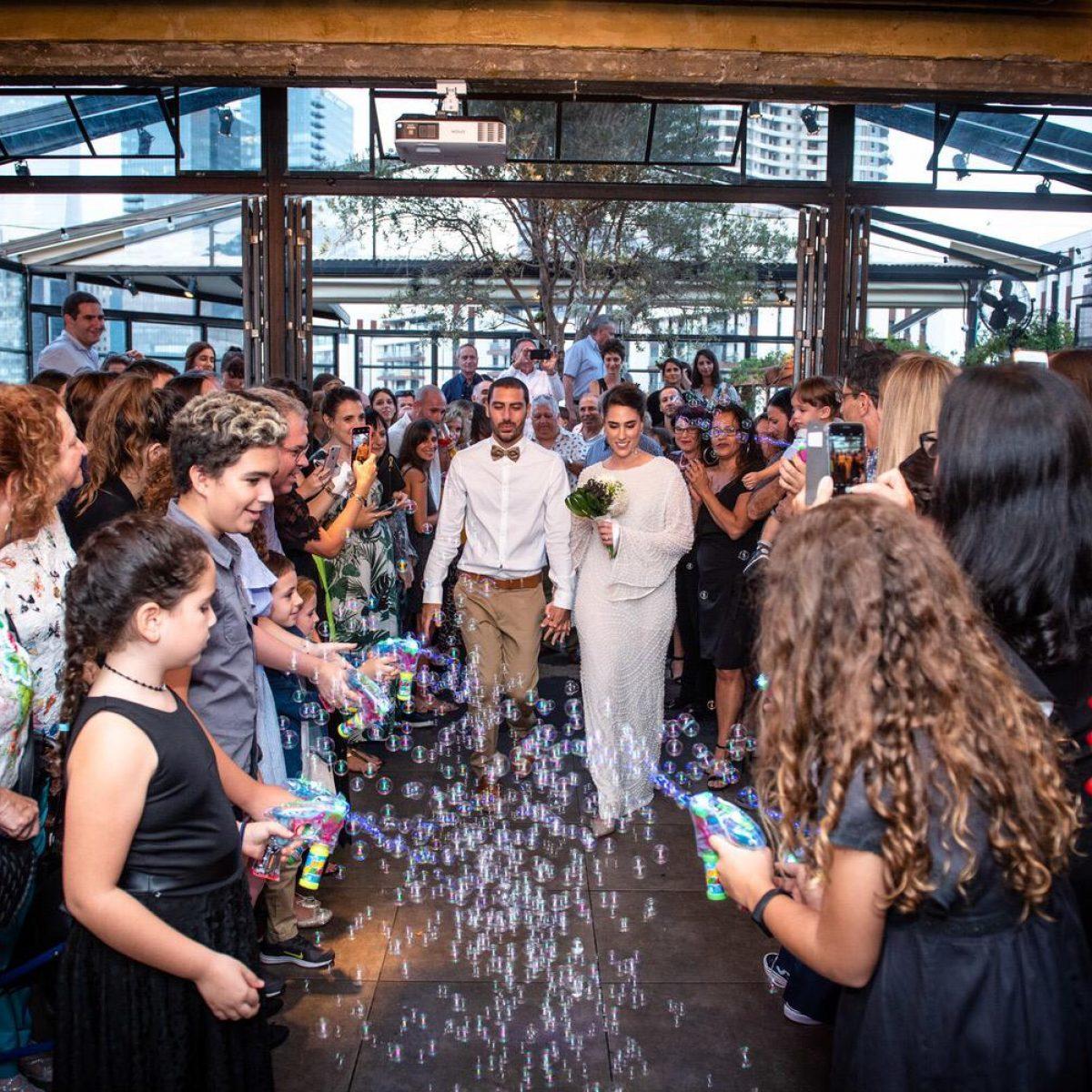אירוע חתונה חתן וכלה נכנסים בעוד ילדים יורים בועות סבון - A wedding event a bride and groom approaching while kids shooting bubbles at the front