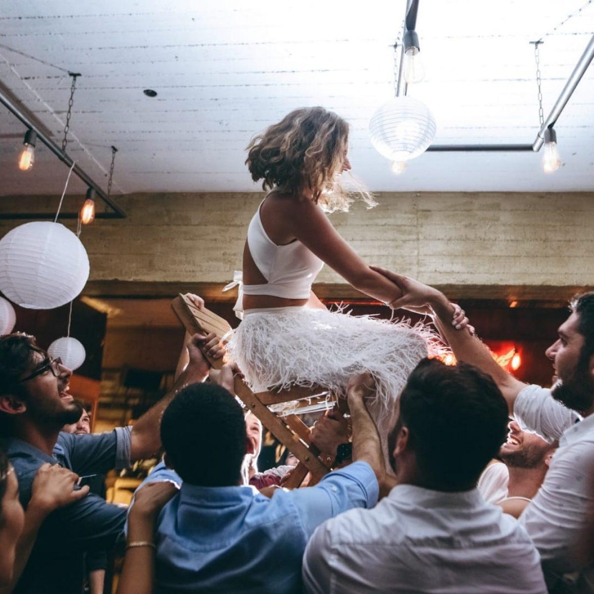חתונה עם כלה מורמת על כיסא ומלא אנשים סביבה - Wedding event with a bride being lifted on a chair and lots of guests around