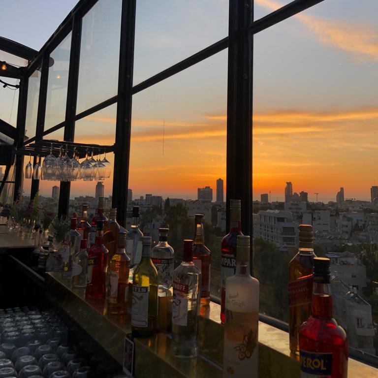 בקבוקים בבר עם נוף משקיף מהחלון - Bottles at the bar view of city from the window