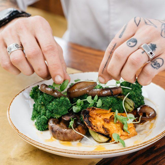 שף מכין צלחת אוכל על שולחן בסורה מרה - Chef is preparing a plate of food on a table at Suramara