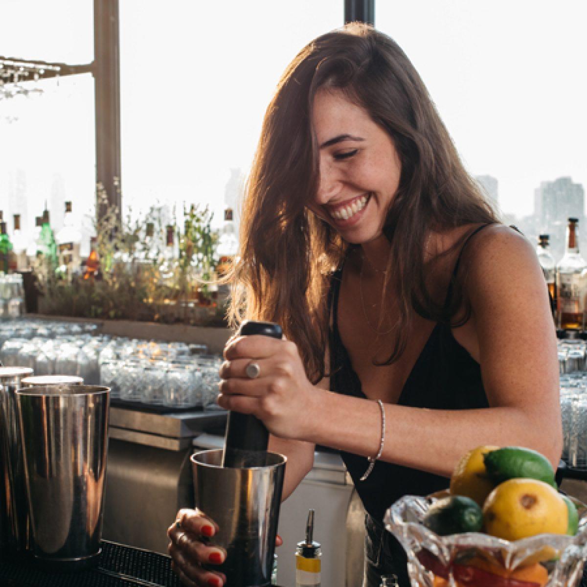 ברמנית מכינה משקה בבר מחוייכת - barwoman preparing a drink at the bar smiling