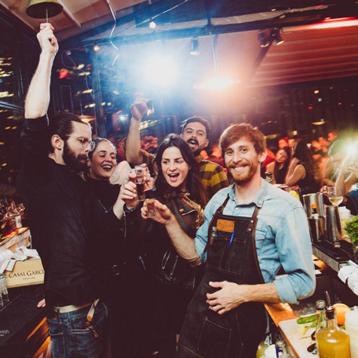 חבורה של אנשים עומדים ליד הבר שמחים, שותים ונהנים - a group of people having fun standing by the bar drinking