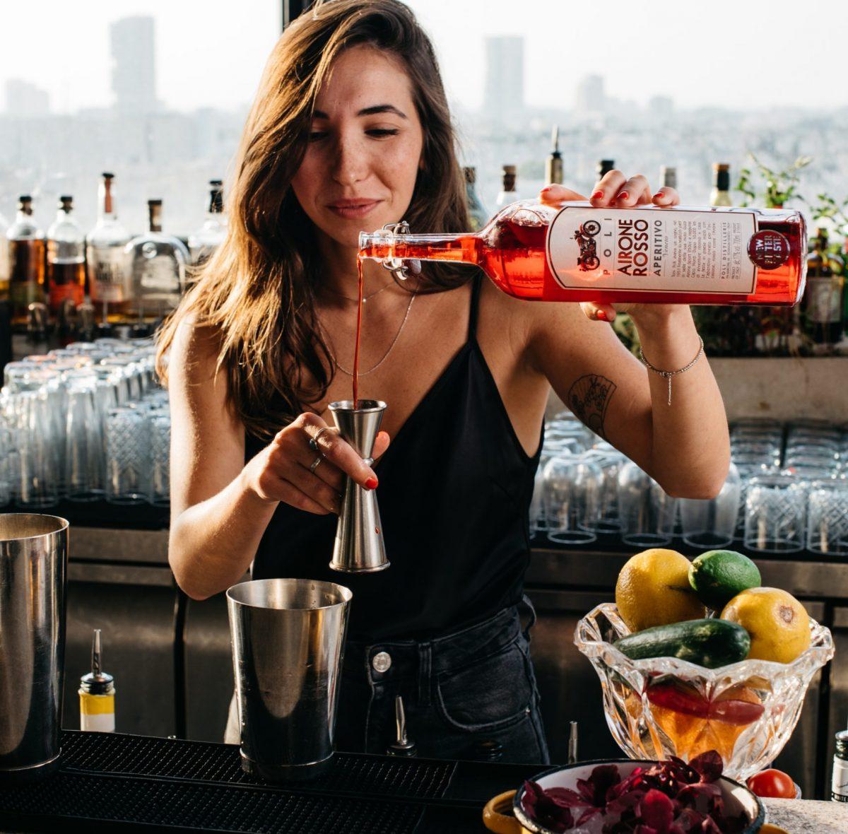 ברמנית מוזגת אלכוהול לכוס בבר בסורה מרה - Barwoman is pouring alcohol at the bar in Sura mara
