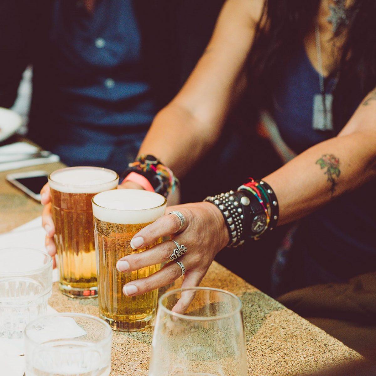 ידיים של אישה עם קעקועים מחזיות 2 כוסות בירה על הבר - Woman's hands with tattoos holding 2 glasses of beer at the bar