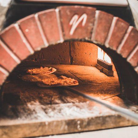 פיצה נכנסת לתוך טאבון של פיצה - Pizza is being placed inside a pizza oven