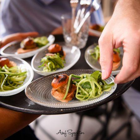 ברמן מחזיק מגש עם צלחות אוכל קטנות - Barman is holding a tray with small dishes