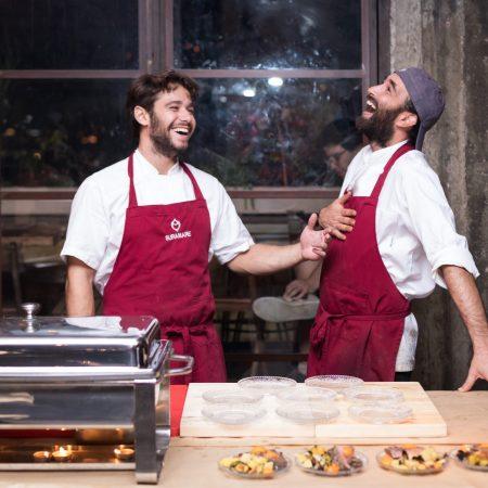 שני טבחים צוחקים צלחות של אוכל לפניהם -Two cooks laughing and food dishes in front of them