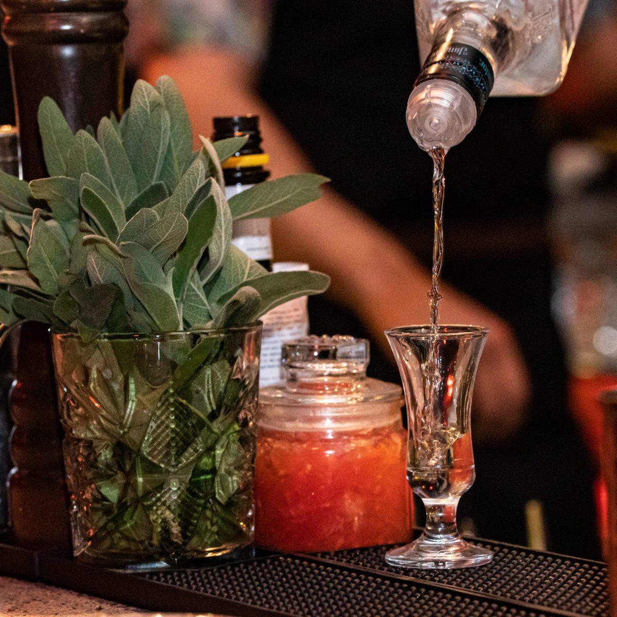 מזיגה של אלכוהול לכוס קטנה על הבר - Alcohol being poured into a shot glass at the bar